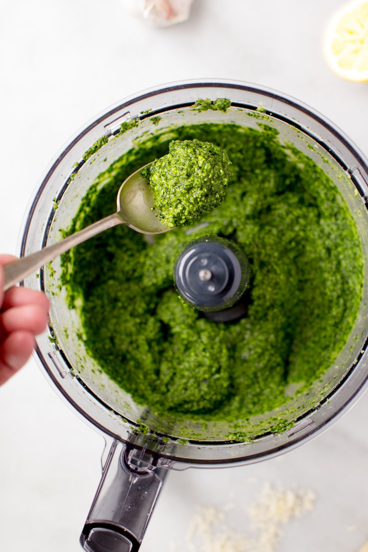 kale pesto in food processor with spoon