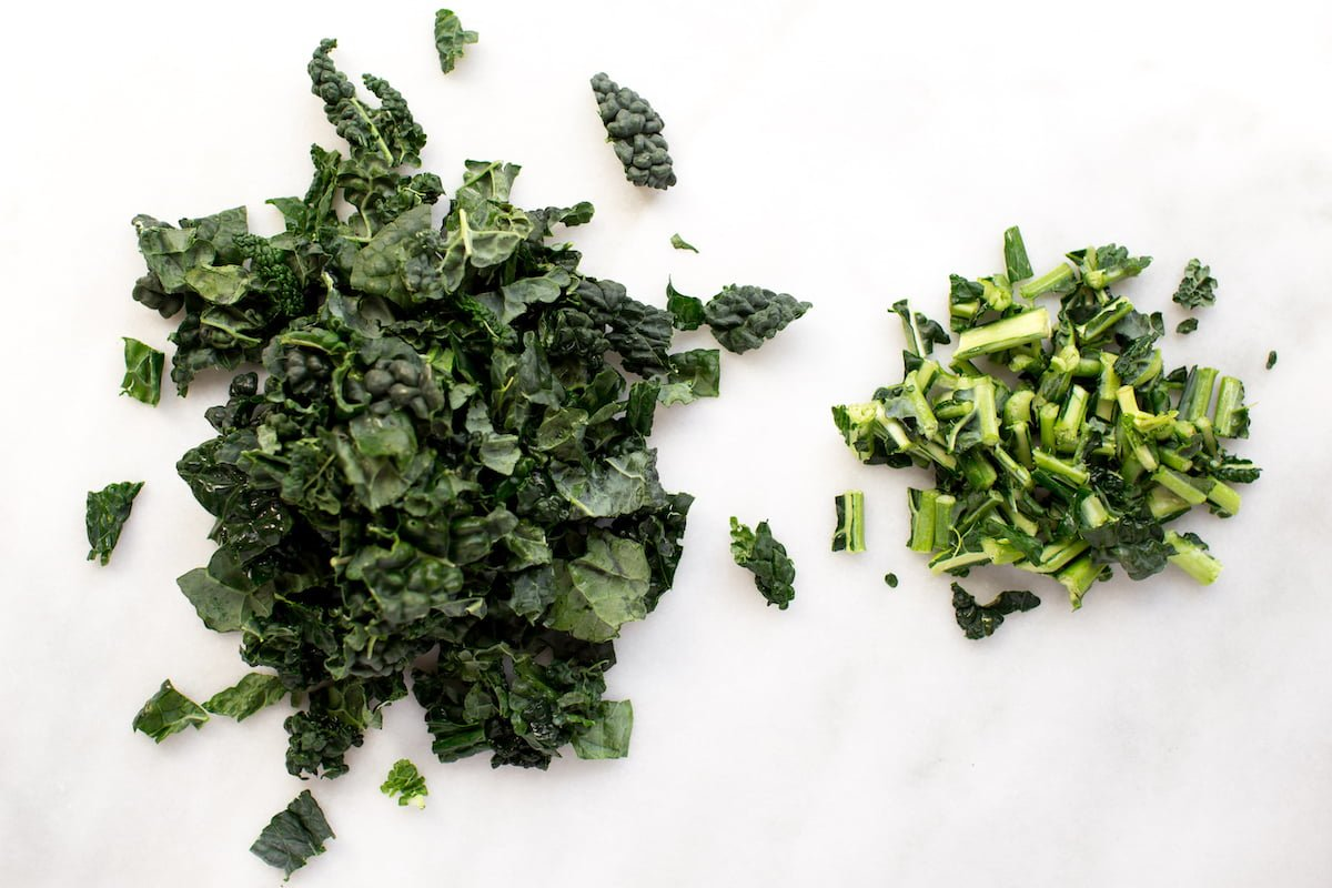 Chopped kale with ribs torn out on marble background