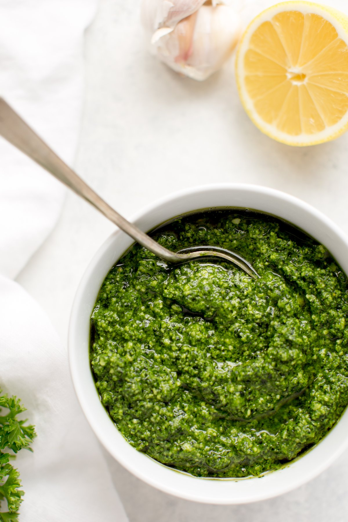 kale pesto in a bowl with spoon and lemon on a white background