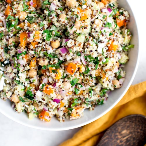 colorful tricolor quinoa salad with parsley, orange bell pepper, chickpeas, red onion with a creamy feta dressing