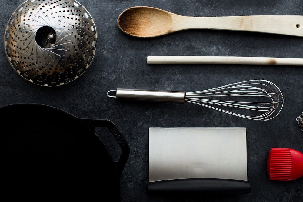 kitchen equipment including whisk steamer wooden spoon bench scraper and cast iron skillet on dark background