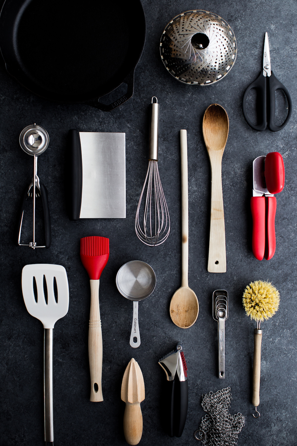essential cooking tools including whisk can opener bench scraper kitchen scissors cast iron skillet measuring cups wooden spoons spatula citrus reamer vegetable brush