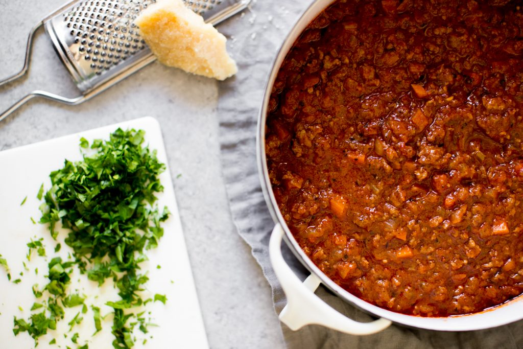 Instant Pot Bolognese sauce in a pot with cheese and parsley for garnish on the side