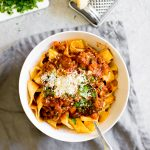 Instant Pot Bolognese pasta and sauce in a bowl with cheese and parsley for garnish
