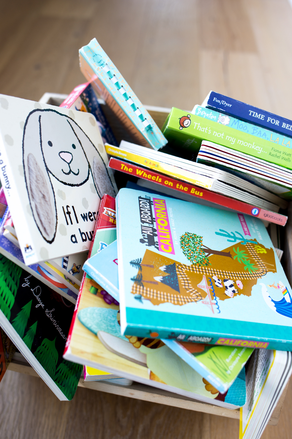 Pile of children's books in a wooden bin