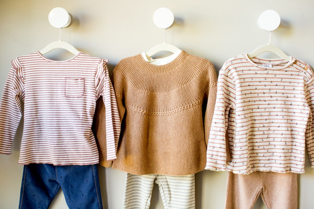 closeup of kids girls capsule wardrobe 3 outfits on hangers