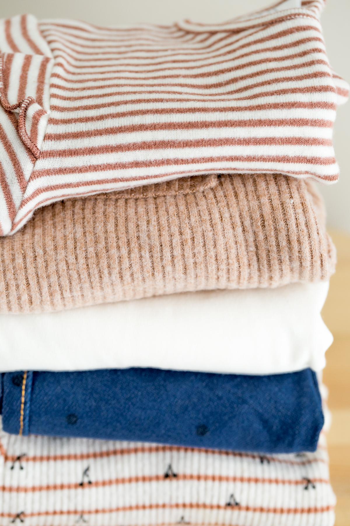 girls capsule wardrobe closeup of folded clothing stacked