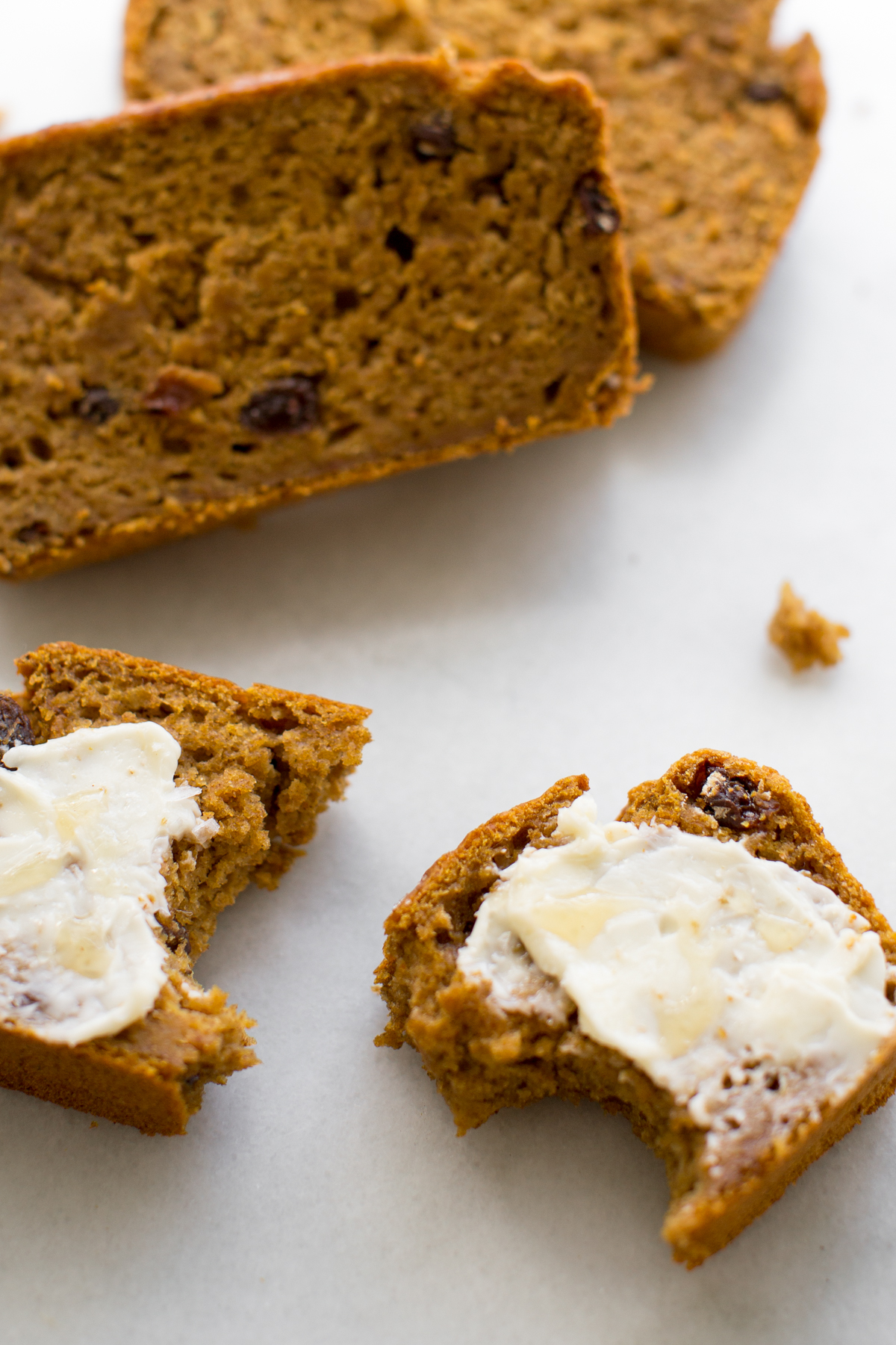 Closeup of a slice of pumpkin bread smeared with butter and a drizzle of honey on a marble background