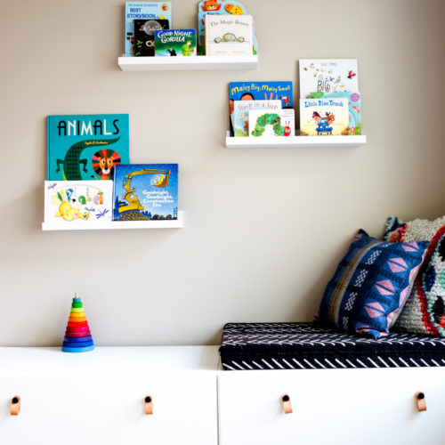 Playroom with white modern toy storage bench IKEA and floating white shelves with kids books