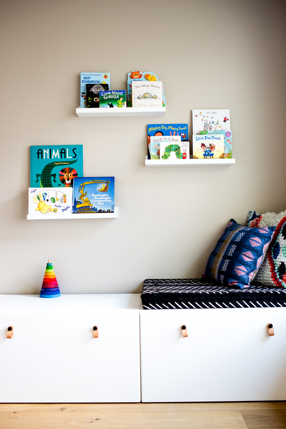 modern playroom with books on floating shelves and white storage drawers with bohemian and african mudcloth style cushions