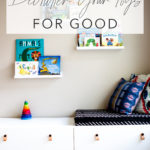 "Play room with white modern toy storage bench IKEA and floating white shelves with kids books and title text ""how to declutter your toys for good"""