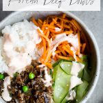 overhead view of healthy korean bulgogi with beef, rice, carrots, cucumber and sriracha crema in gray ceramic bowl with healthy korean beef bowls as text overlay