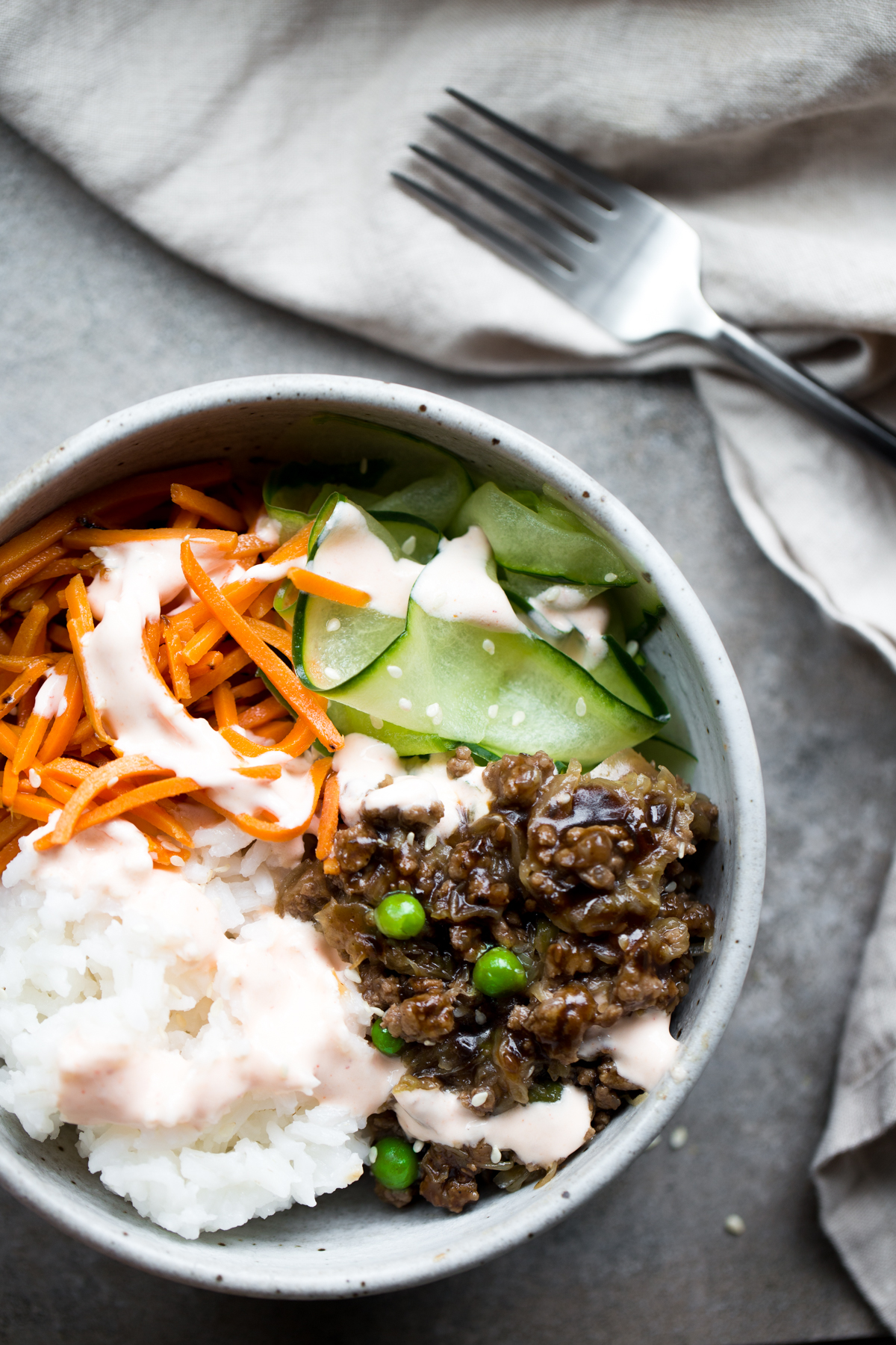 overhead view of korean bulgogi with beef, rice, carrots, cucumber and sriracha crema in gray ceramic bowl with gray background napkin and fork