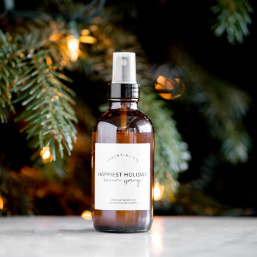bottle of homemade essential oil holiday room spray with a lit tree in the background title text overlay