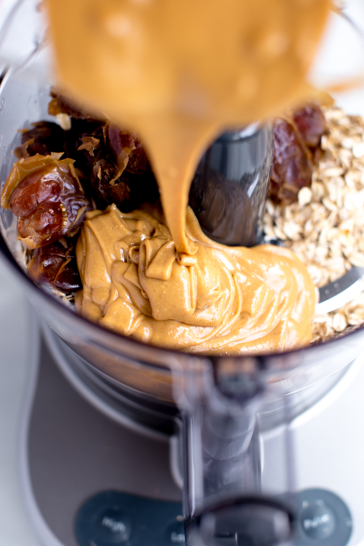 ingredients for no-bake peanut butter snack bite cookie dough in food processor with peanut butter drizzle
