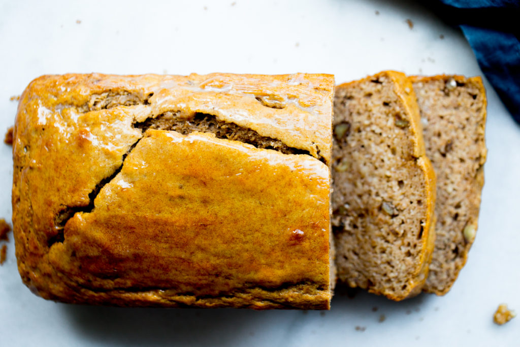 overhead shot of sliced banana bread loaf on marble background with blue napkin