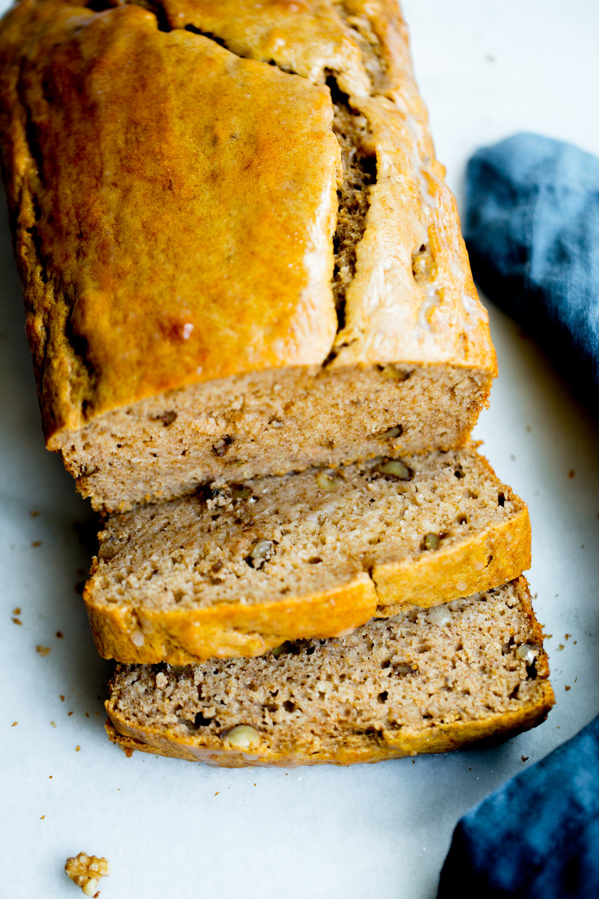 close up photo of a loaf of healthy banana bread with walnuts on marble background with a blue napkin