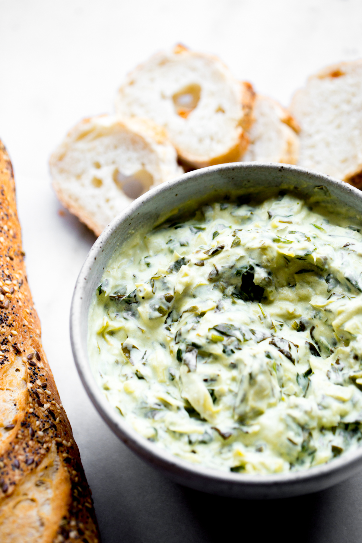 45 degree angle photo of creamy instant pot spinach artichoke dip with sliced baguette on white marble background