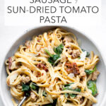 instant pot sausage sun-dried tomato pasta overhead in a gray bowl with title text overlay