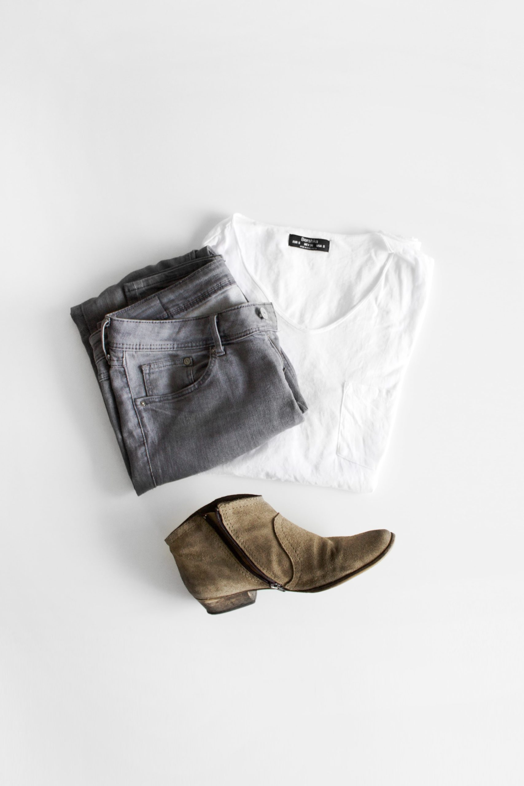 overhead flatlay of womens minimalist clothing on white background