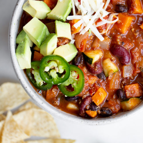 closeup overhead shot of a bowl of vegan vegetarian quinoa chili on marble background with tortilla chips and cilantro