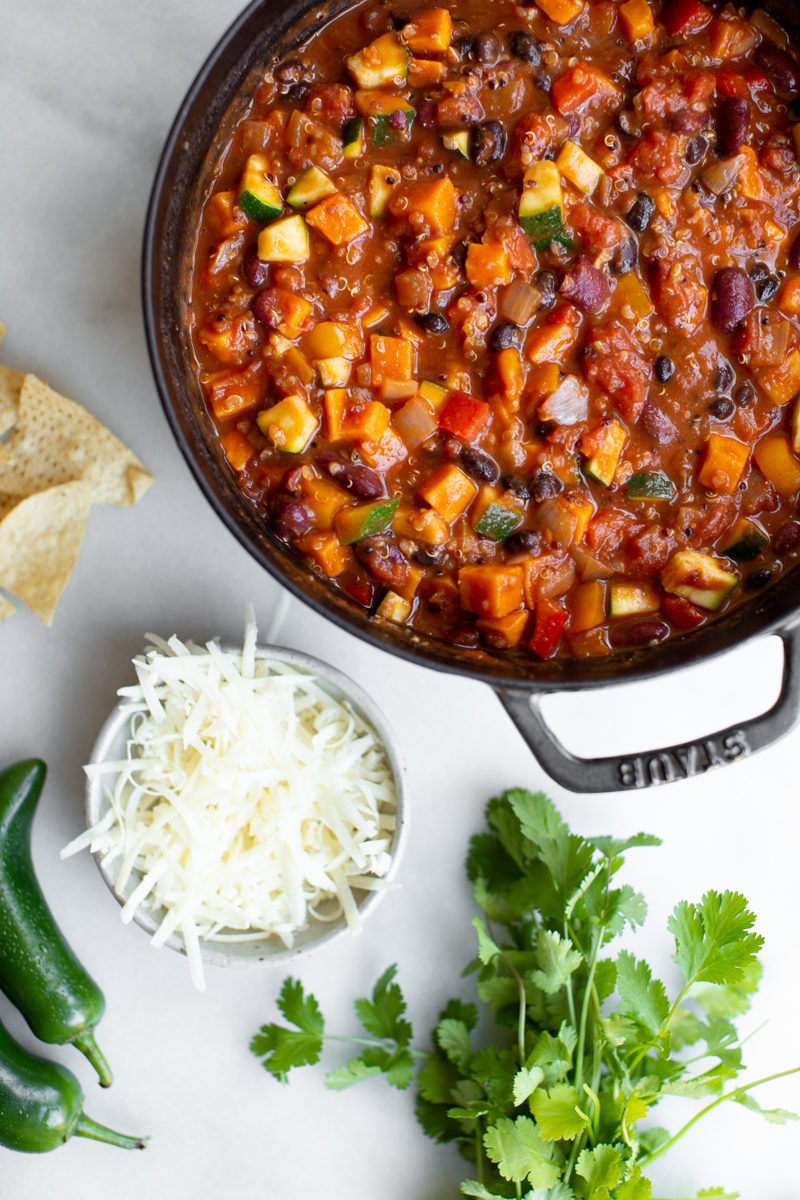 large pot of vegetarian sweet potato quinoa chili on white marble background with jalapeños, tortilla chips, cheese, and cilantro