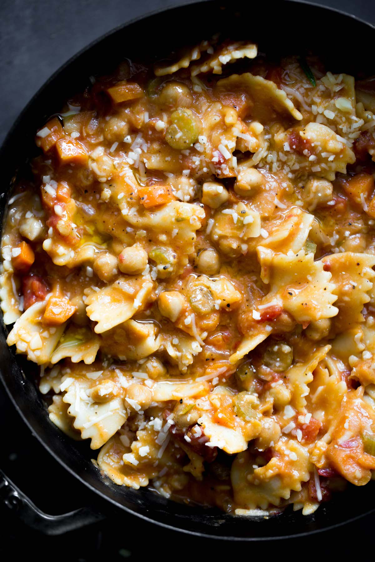 closeup photo of vegetarian pasta e ceci (pasta and chickpeas) in a big pot with dark gray background
