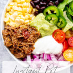 overhead photo of a burrito bowl with instant pot Mexican shredded beef corn black beans, lettuce, tomatoes, diced red onion sour cream jalapenos and avocado sauce on a concrete background with title text overlay