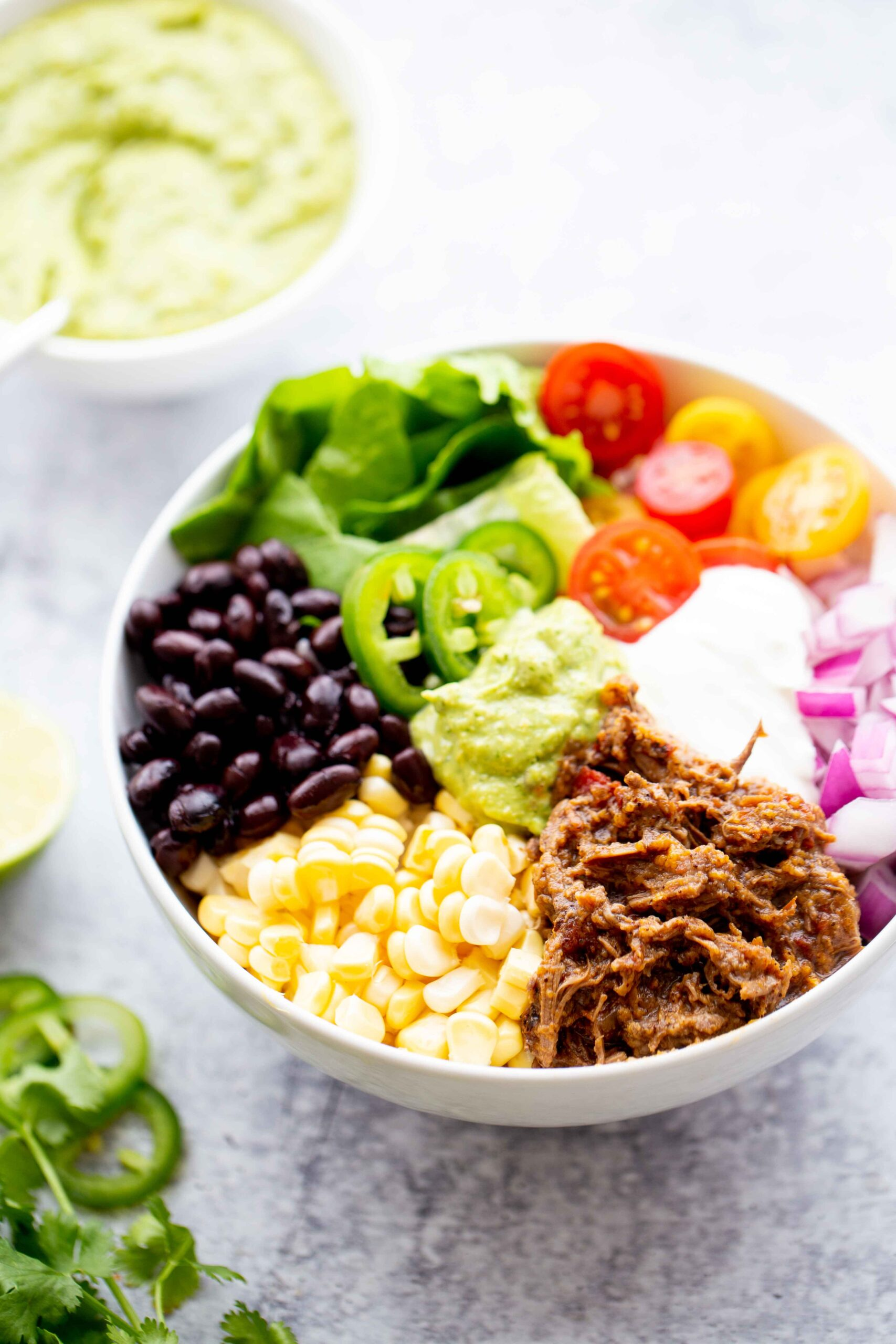 45 degree photo of a backlit burrito bowl with shredded beef corn black beans lettuce tomatoes diced red onion sour cream jalapeños and avocado sauce on a concrete background with a bowl of avocado sauce in the background