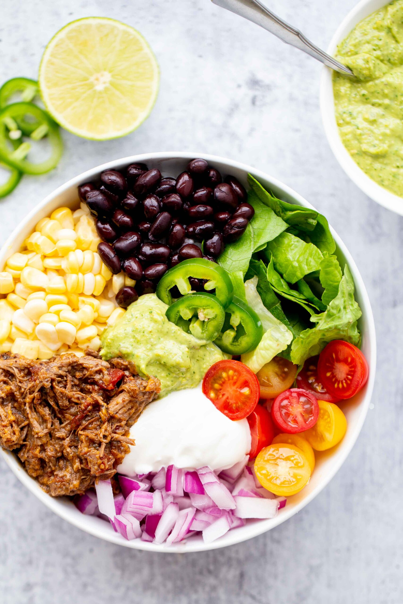 overhead photo of a burrito bowl with shredded beef corn black beans lettuce tomatoes diced red onion sour cream jalapeños and avocado sauce on a concrete background
