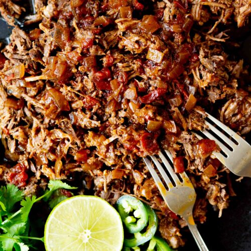 closeup overhead photo of instant pot Mexican shredded beef on a black cutting board with cilantro lime and jalapeño and two forks and instant pot in the background