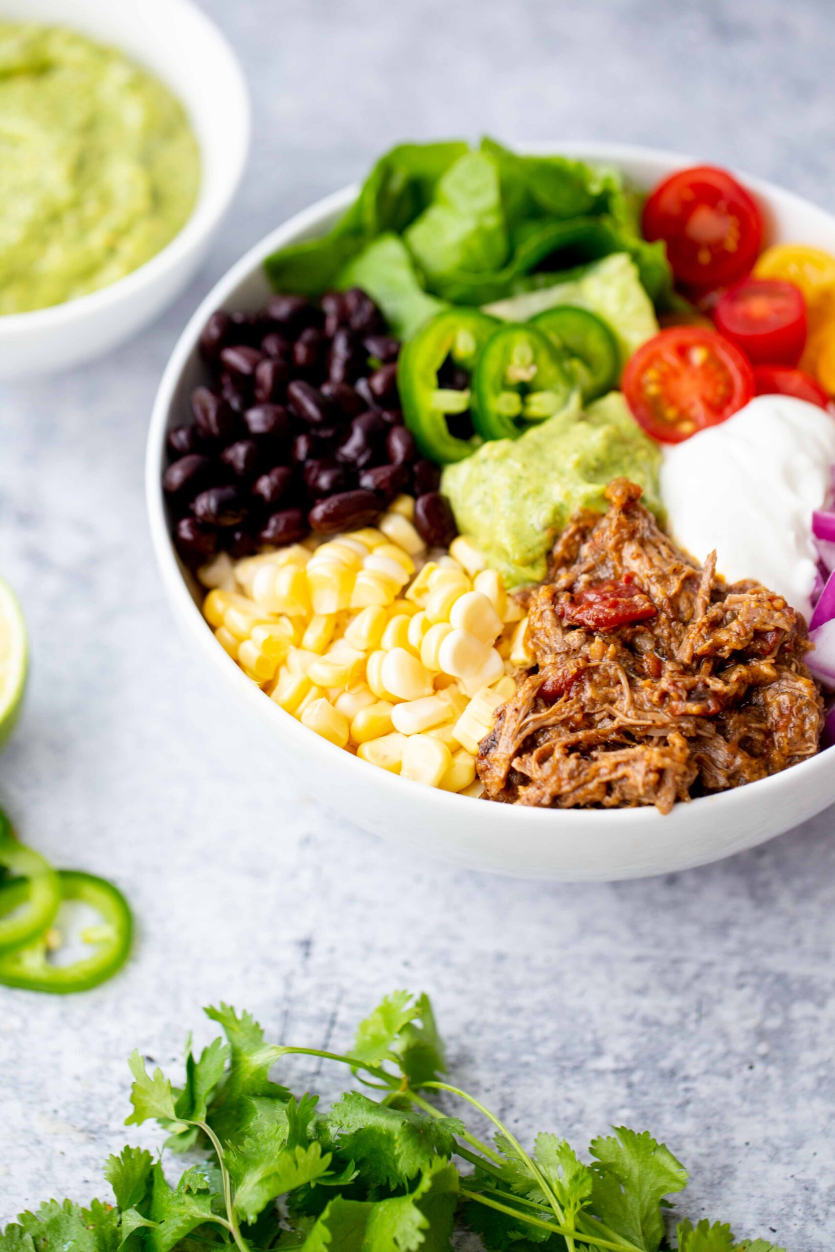 45 degree photo of a burrito bowl with instant pot shredded Mexican beef corn black beans lettuce tomatoes diced red onion sour cream jalapeños and avocado sauce on a concrete background with a bowl of avocado sauce in the background