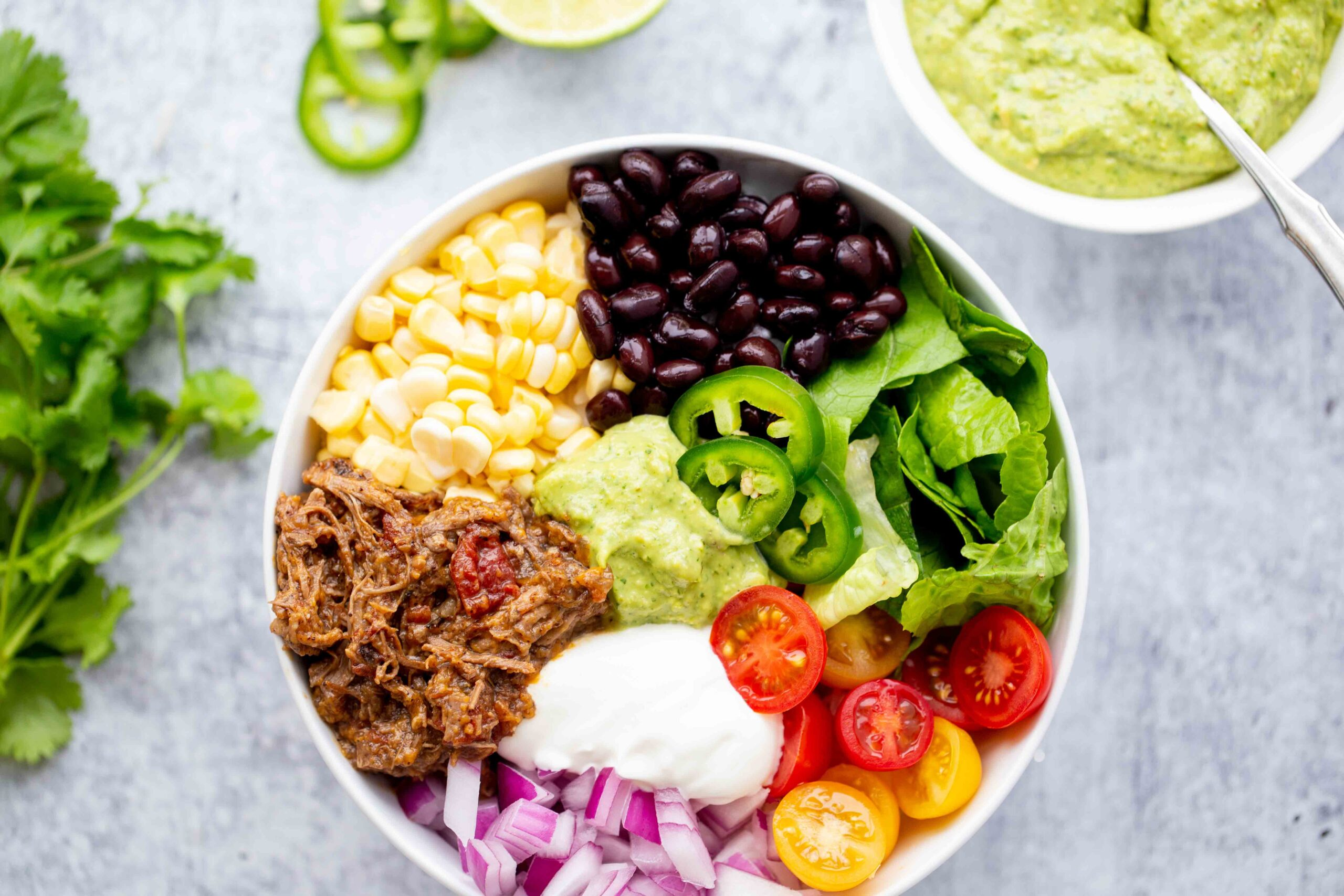 closeup overhead photo of a burrito bowl with shredded beef corn black beans lettuce tomatoes diced red onion sour cream jalapeños and avocado sauce on a concrete background with a bowl of avocado sauce in the background