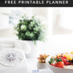 how to simplify meal planning modern minimalist bright image with cookbooks, bowl of fruit, pen and meal planner with title text overlay