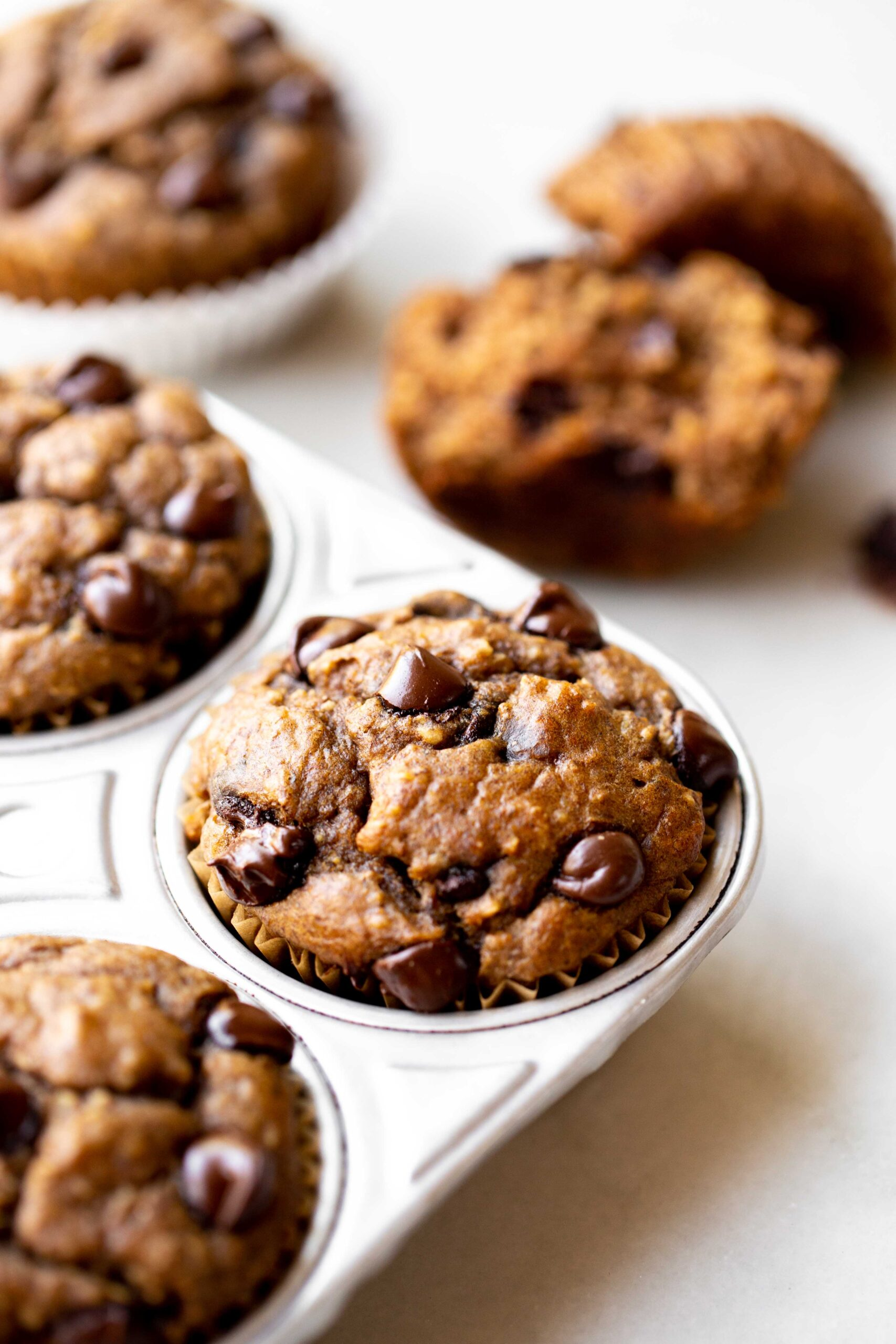 closeup photo at 45 degree angle of freshly baked healthy chocolate chip banana muffins in an aluminum muffin pan on a light gray marble background