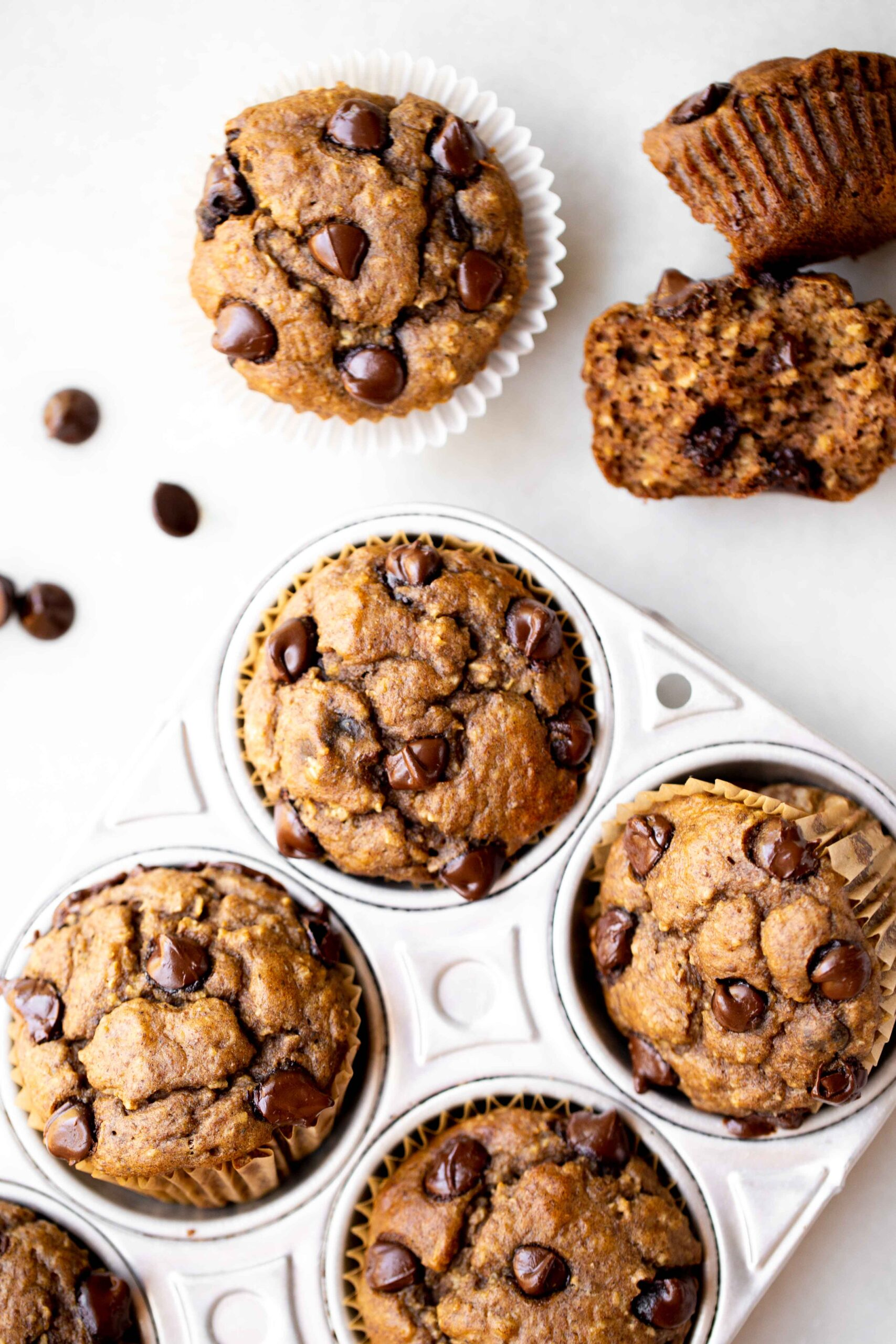overhead photo of freshly baked healthy chocolate chip banana muffins in an aluminum muffin pan with milk and chocolate chips in the background