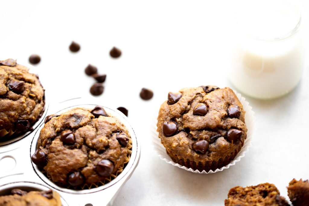 backlit photo of freshly baked chocolate chip banana muffins in an aluminum muffin pan with milk and chocolate chips in the background