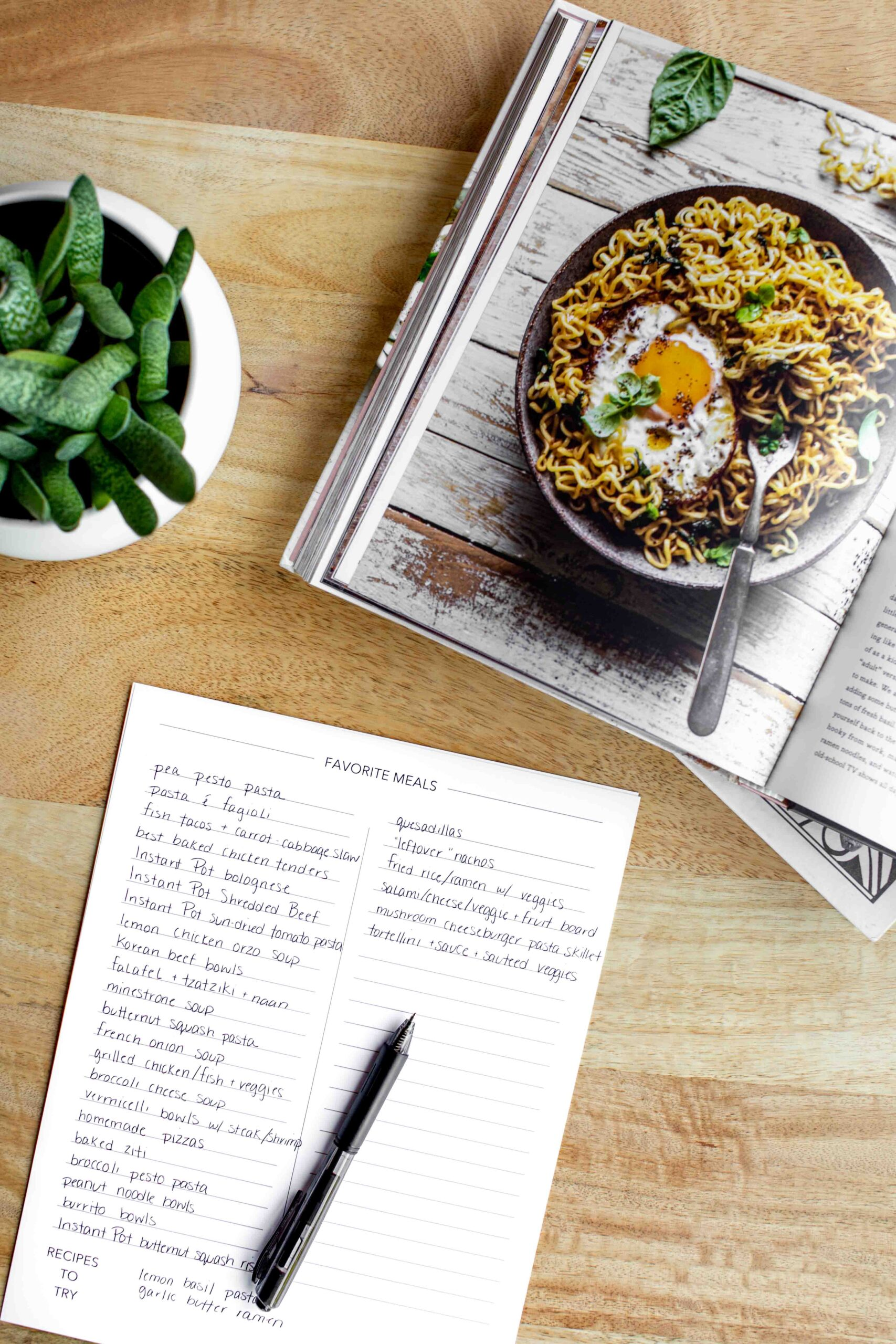 overhead photo of meal planner master meal list with a pen cookbook and plant on a wood table