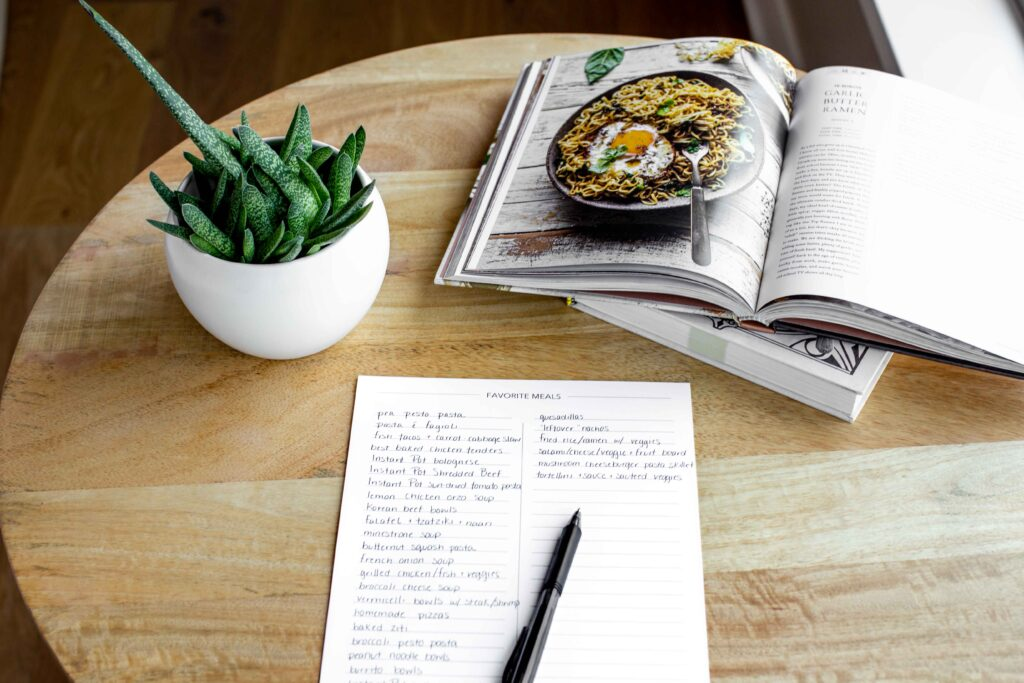side angle photo of meal planner master meal list with a pen cookbook and plant on a wood table
