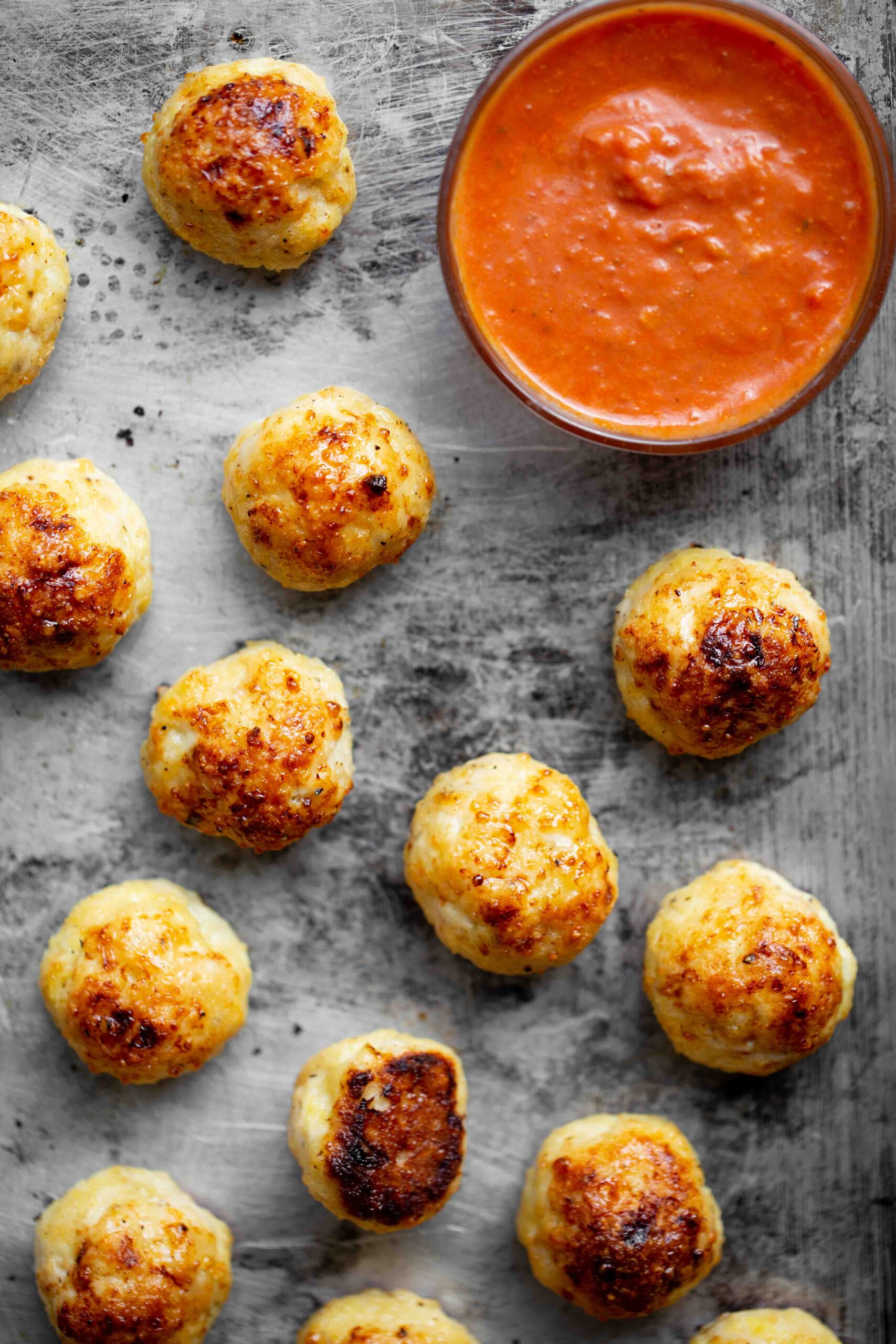 Overhead photo of baked chicken meatballs on a sheet pan with red marinara sauce