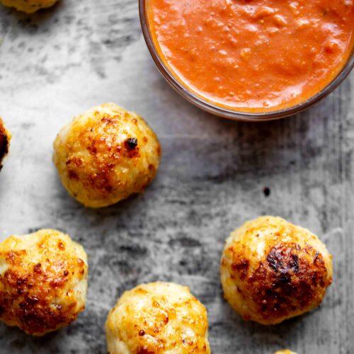 Overhead closeup of baked chicken meatballs on a sheet pan with red marinara sauce