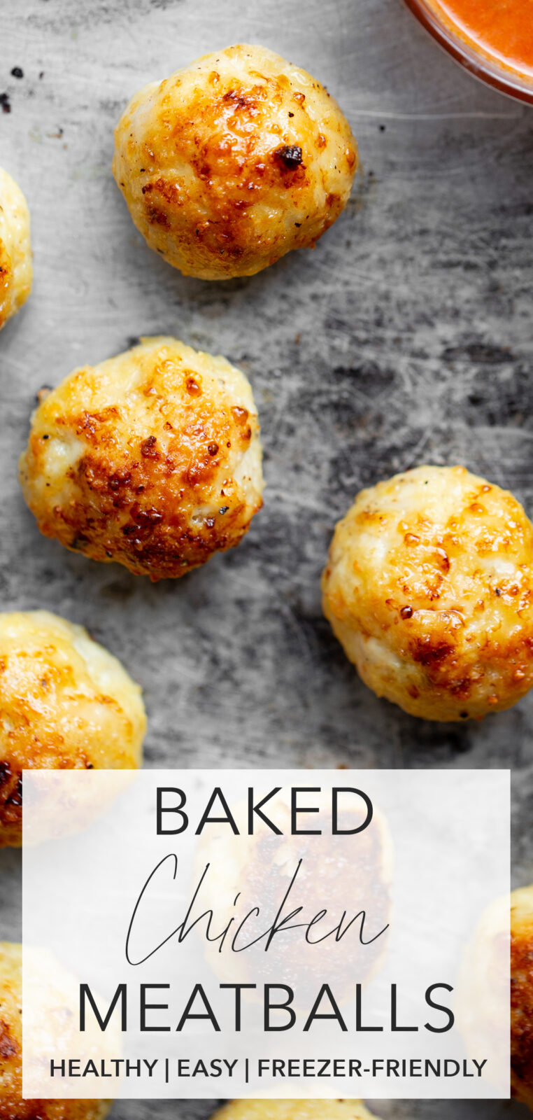 Overhead photo of baked chicken meatballs on a sheet pan with a bowl of tomato sauce with title text overlay