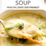 closeup photo of a spoonful of creamy broccoli cauliflower cheese soup with carrot and white beans with title text overlay
