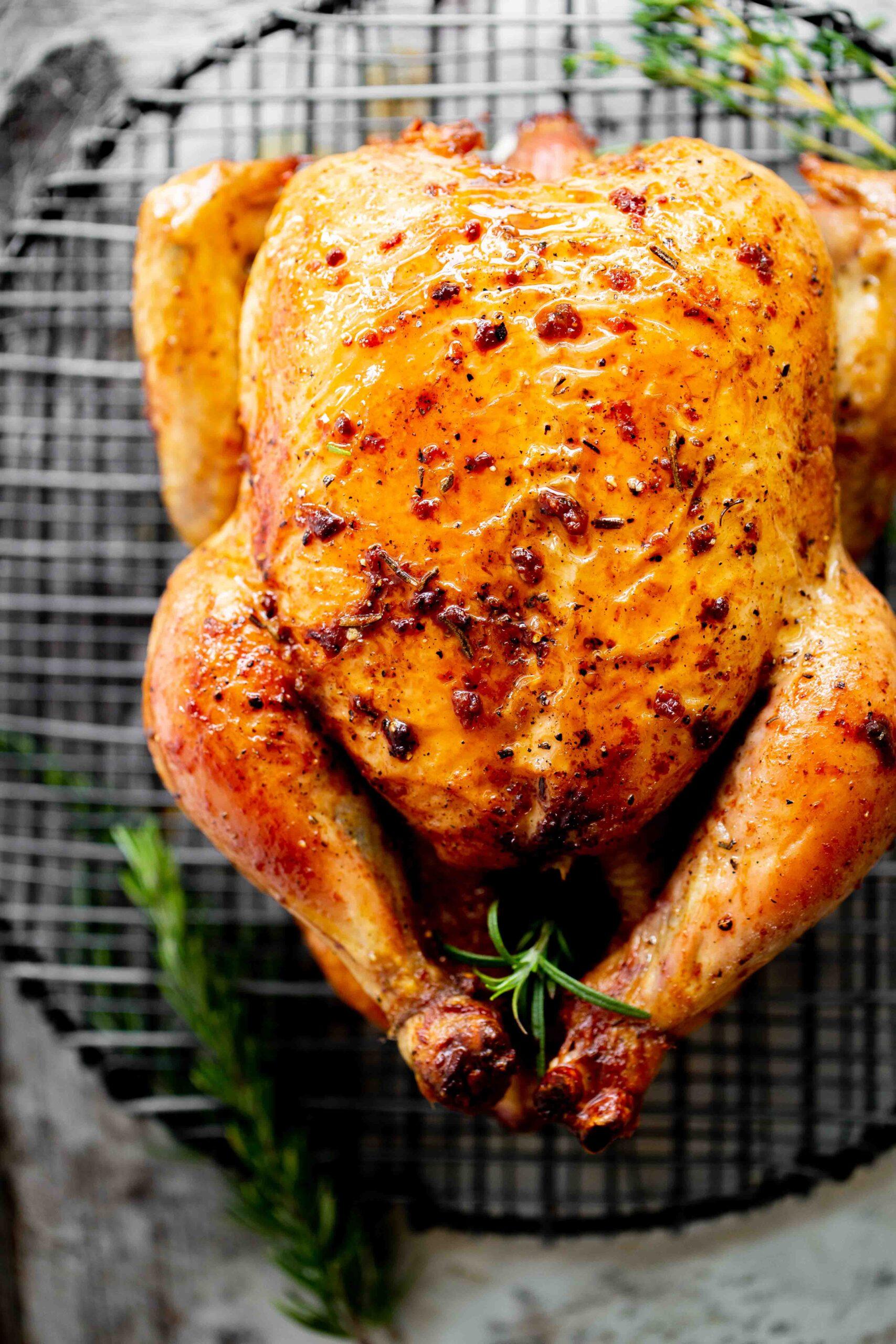 overhead photo of juicy cast iron roast chicken with crispy skin on black metal rack