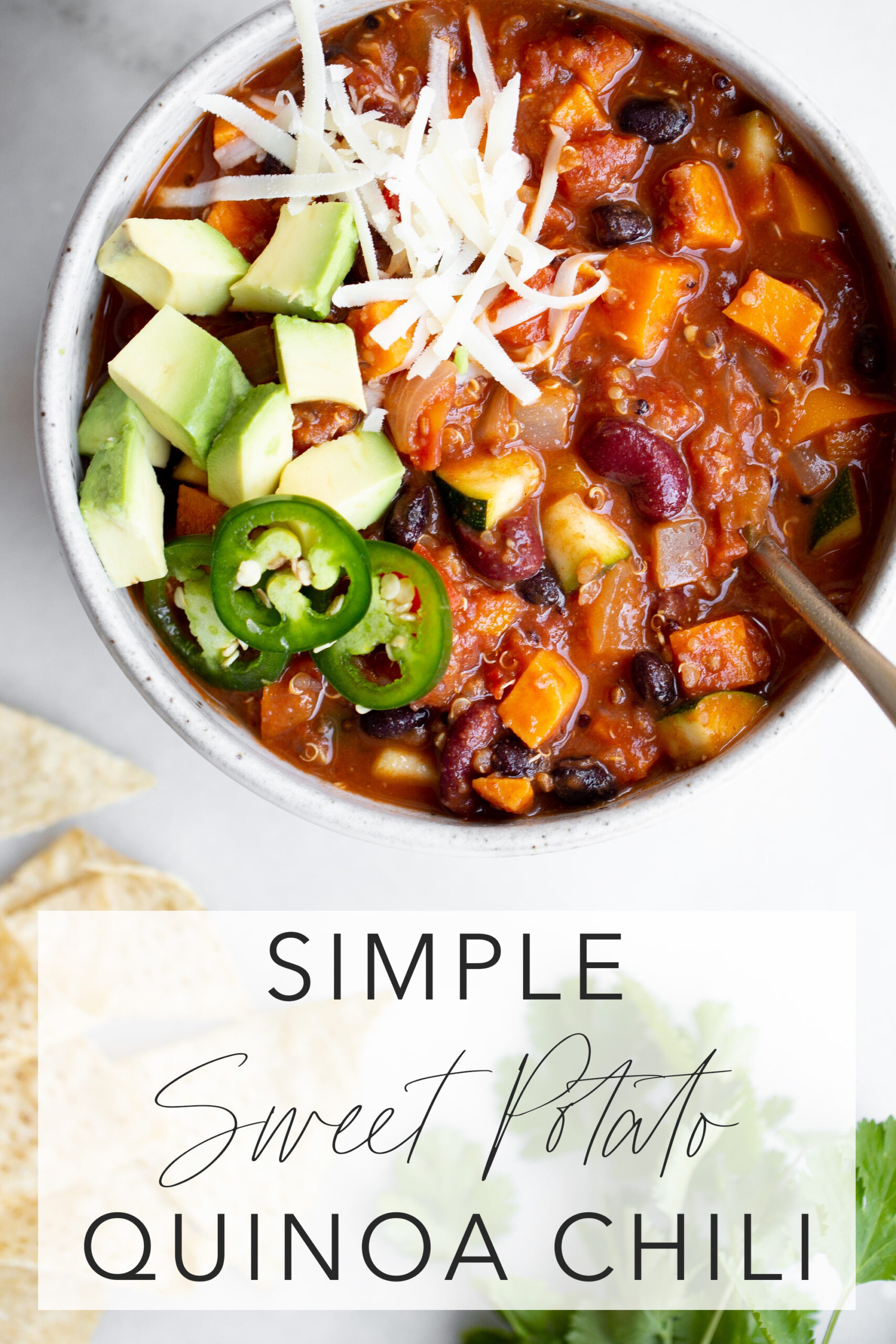 overhead photo of a bowl of sweet potato quinoa chili with avocado, cheese, jalapeños, and tortilla chips with title text overlay