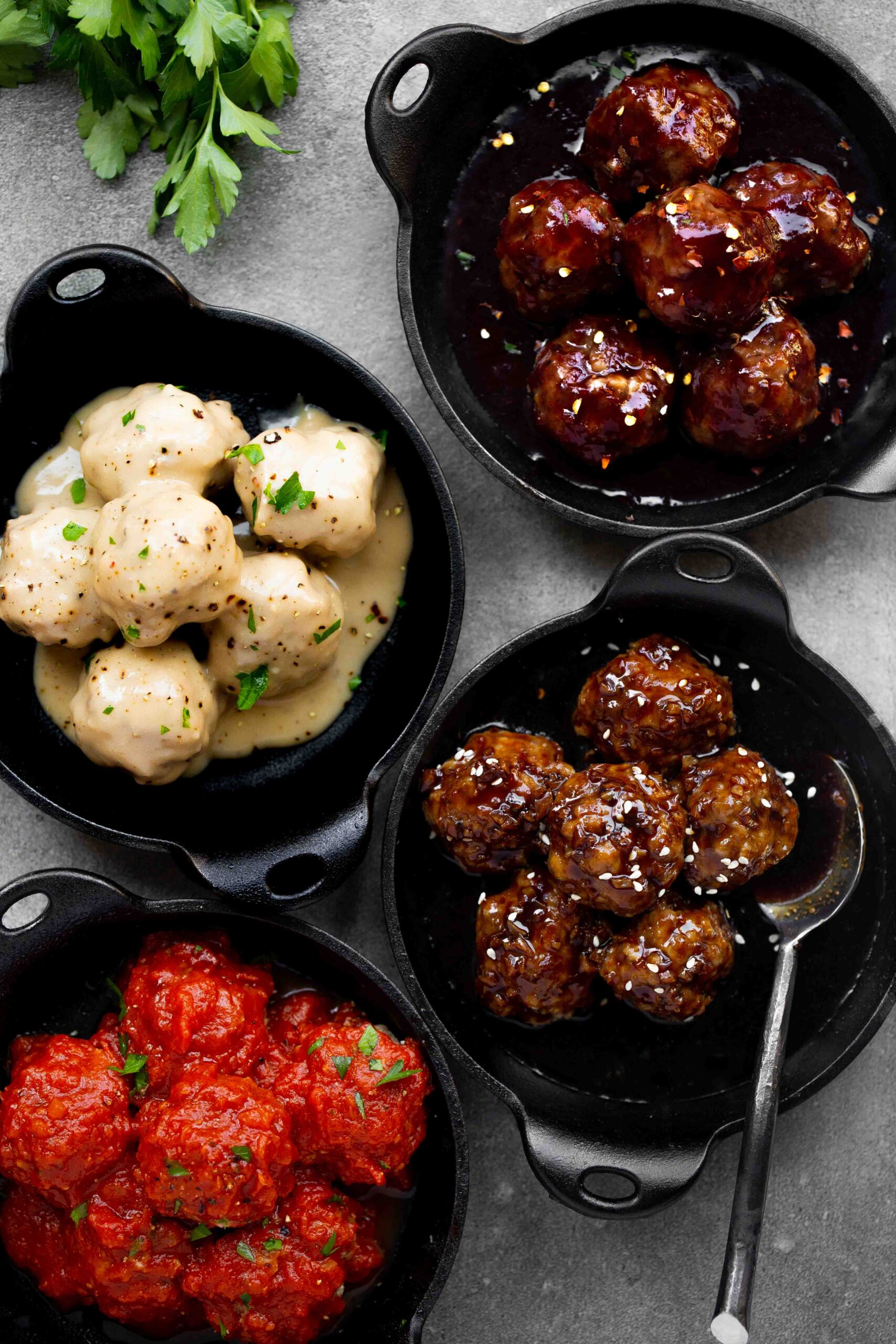 overhead photo of instant pot meatballs in cast iron skillets in four different sauces: sweet and sour with grape jelly, swedish meatball gravy, korean bbq sauce, and meatballs in marinara sauce