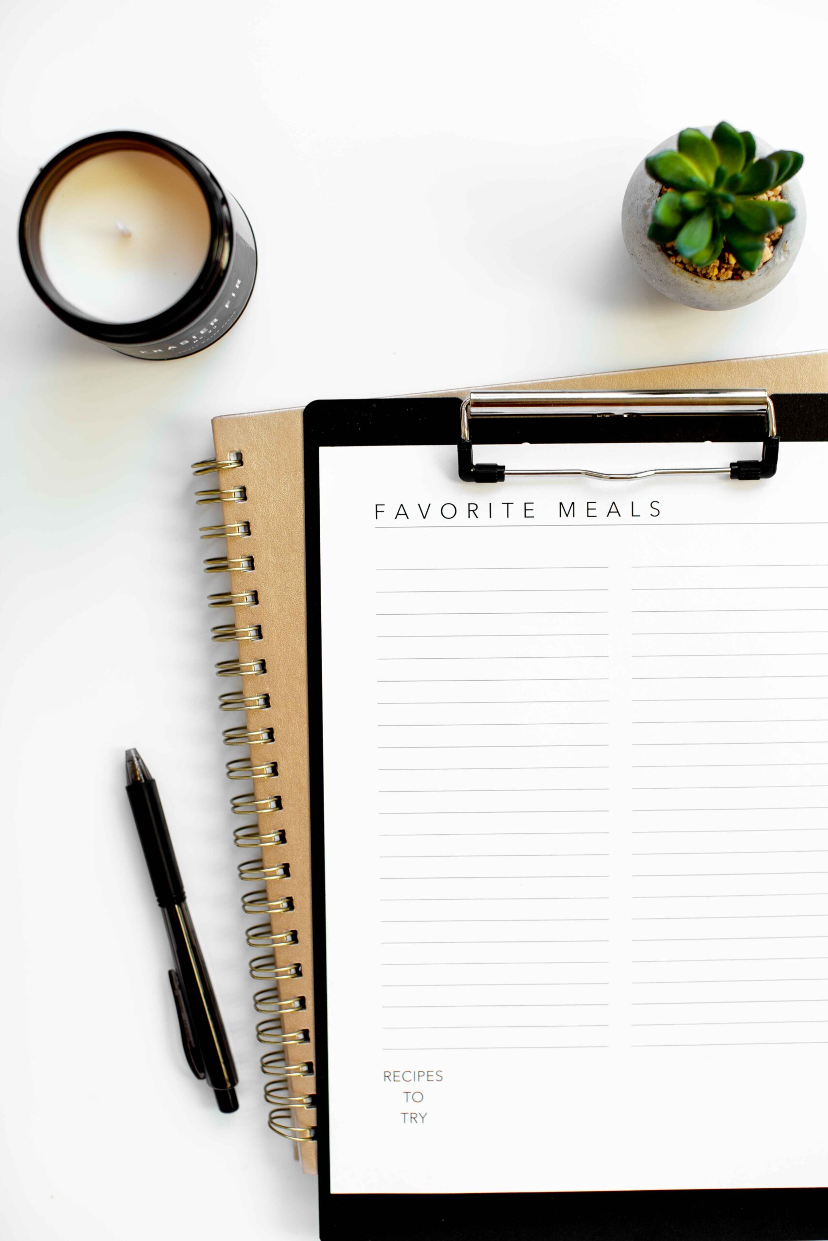 overhead photo of meal planning printable worksheet on white background with pen plant candle