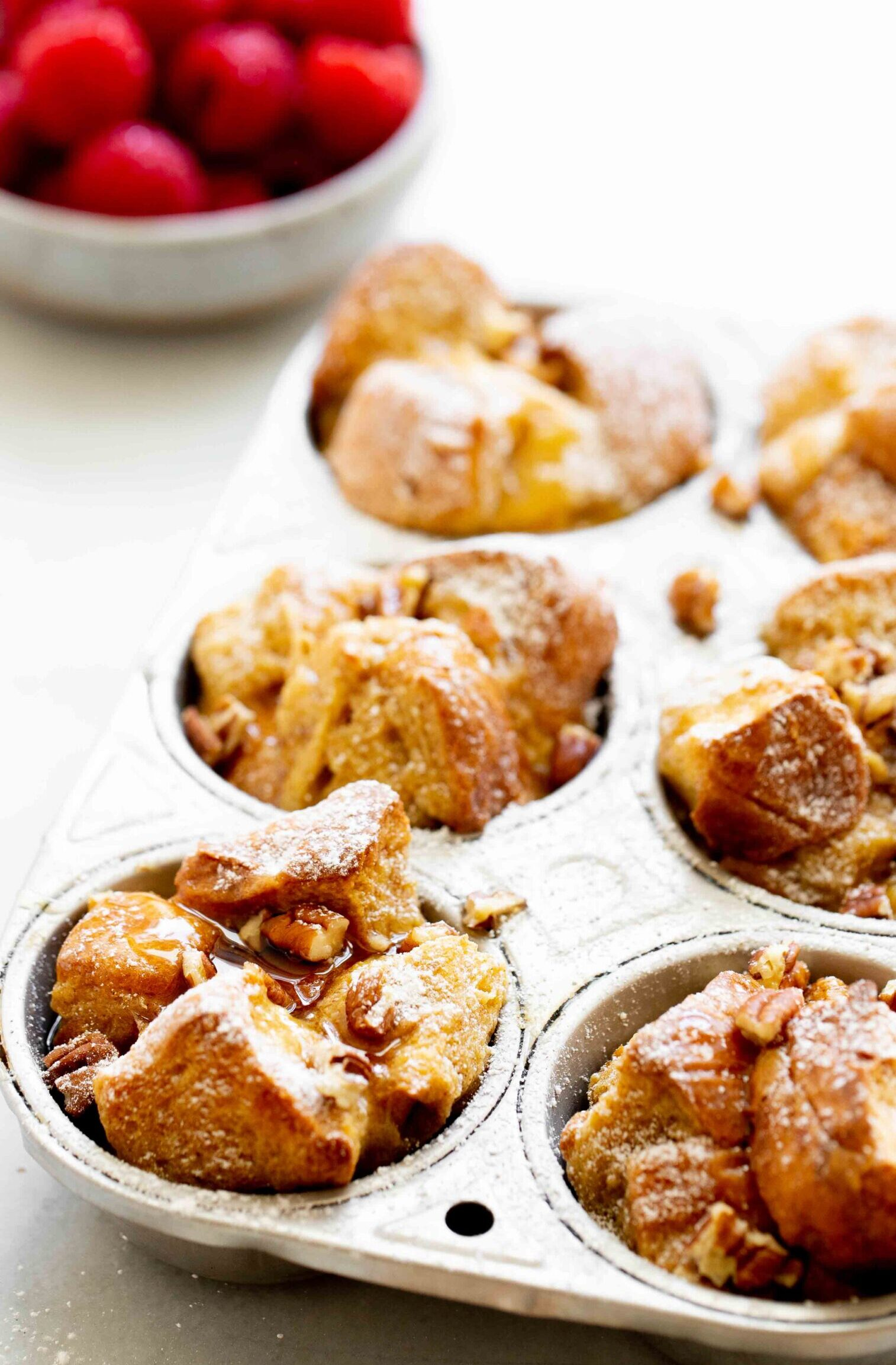 closeup photo of french toast muffins in aluminum muffin tin with a bowl of raspberries in the background