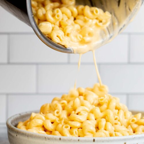 Instant Pot mac and cheese recipe with pasta being poured from pot into serving bowl